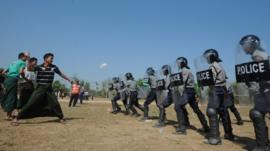 People throw water bottles at riot control policemen during a European Union (EU) crowd management training session