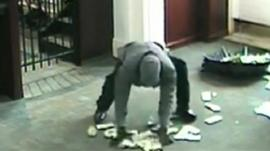 Thief picks up money from floor