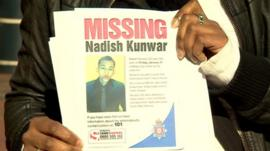 Friend holds poster of missing Nadish Kunwar