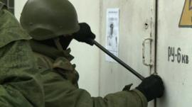 Soldier using crowbar on door
