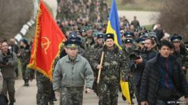 Colonel Yuli Mamchor (L), commander of the Ukrainian military garrison at the Belbek airbase, leads his unarmed troops to retake the Belbek airfield from soldiers under Russian command in Crimea