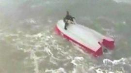 Man sits on upturned boat with dog