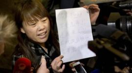 A relative of a Chinese passenger aboard the missing Malaysia Airlines Flight MH370 shows a paper reading