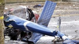 The wreckage of a news helicopter sits on a city street after crashing Tuesday, March 18, 2014, in Seattle