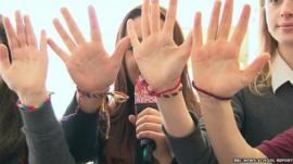 Girls holding up palms wearing rainbow bracelets