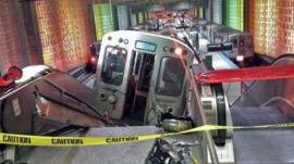 A Chicago Transit Authority train car rests on an escalator at the O'Hare Airport station after it derailed early Monday