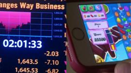 split screen of shares and Candy Crush Saga on mobile
