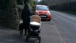 Blind woman with push chair and guide dog near car parked on pavement