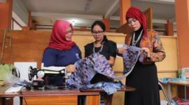A piece of batik cloth is inspected at the prison workshop