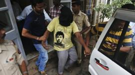 Police officers escort a man (face covered) arrested in connection with the gang rape of a photo journalist in Mumbai