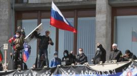 Pro-Russian activists who seized the main administration building in the eastern Ukrainian city of Donetsk deploy a flag of the so-called Donetsk Republic and hold a Russian flag on April 7, 2014, in Donetsk