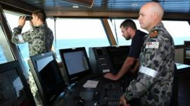 A 5 April 2014 image shows Commander James Lybrand (R), mission commander on the Australian Defence Vessel Ocean Shield, with Captain Nick Woods (C), master of the ship during the search for missing Malaysia Airlines flight MH370, in the southern Indian Ocean