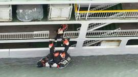 A passenger is rescued by South Korean maritime policemen