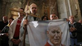 Polish pilgrims hold a flag portraying Pope John Paul II during a vigil prayer