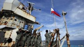 Marines stationed aboard a Philippine ship grounded on a disputed reef, the Second Thomas Shoal, take part in a flag ceremony on 29 March 2014