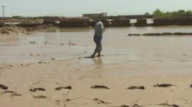 Afghan man walking through the mud after the floods in north of the country