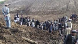 Afghan villagers gather at the site of a landslide at the Argo district in Badakhshan province