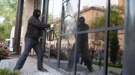 A pro-Russian activist breaks the glass of offices of the Industrial Union of Donbass Corporation in Donetsk