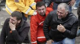 Relatives of miners who were killed or injured in a mine explosion react as rescuers work in Soma