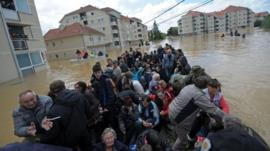 A group is evacuated on an amphibious vehicle over flooded streets in the town of Obrenovac