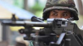 A Thai army soldier stands guard on a city centre street after martial law was declared on May 20