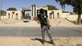 A militia stands guard in front of the entrance to the February 17 militia camp after Libyan irregular forces clashed with them in Benghazi, 16 May 2014