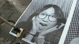 A selfie of a woman pasted on to a pavement