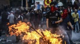 Protesters wearing masks by fire in street