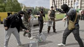 Pro-Russian militants smash ballot boxes in front of the seized regional administration building in Donetsk