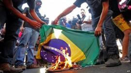 Protesters burning Brazilian flag