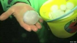 Hand holds bucket of giant hail stones in Wilber, Nebraska