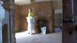 Plaster being removed from a wall