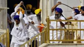 Sikhs wield ceremonial swords at the Golden Temple