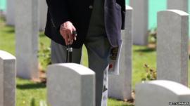 War veteran walking past graves