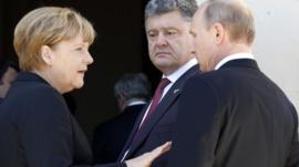 German Chancellor Angela Merkel (L), Ukrainian President-elect Petro Poroshenko and Russian President Vladimir Putin (R)