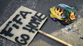 'Fifa go home' sign next to burning Brazilian flag