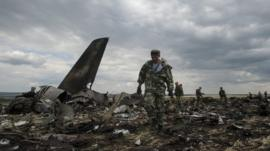 Pro-Russian fighters walk at the site of a downed Ukrainian army aircraft