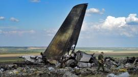 Pro-Russian militants look through the debris of Ukrainian plane site
