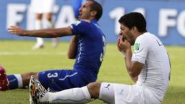 Giorgio Chiellini holds his shoulder after allegedly being bitten by Luis Suarez