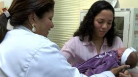 Nurse handing a mother her newborn baby