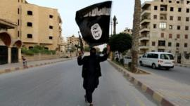 A gunman in the Syrian city of Raqqa waves an Isis flag - 29 June 2014