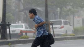Man hurrying through rain and wind