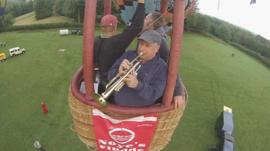 A trumpeter in a hot air balloon basket
