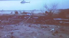 Amateur video of Air Algerie flight AH5017 crash site, showing helicopter over debris