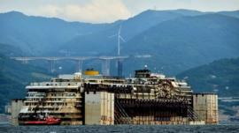 Refloated wreck of the Costa Concordia being dragged to the harbour near Genoa