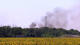Smoke rises on the outskirts of Donetsk over sunflower field