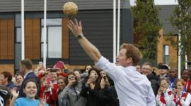 Prince Harry plays a game during a visit to the Commonwealth Games Village