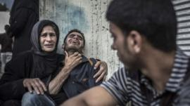 Palestinians mourn the death of a relative, who died when a UN school used as a shelter for internally displace people came under Israeli shelling in the Kamal Adwan hospital in Beit Lahia,