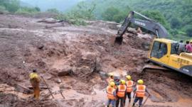 A handout photograph from the Maharashtra state government shows diggers working at the site of a landslide in the village of Malin in Pune