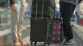 People with luggage on a travellator